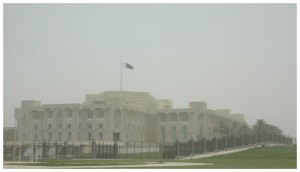A large white building behind an iron fence.