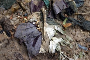 Clothes, teeth and bone fragments exposed after the rain at the site of a mass grave.
