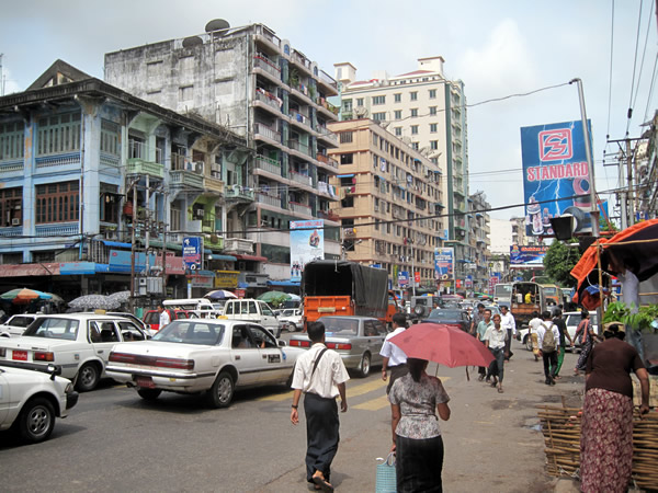 Old buildings, vehicles, and pedestrians in central Yangon