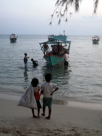 Two small children, a girl on the left of the picture and a boy on the right, stand on the beach. It is dusk, and they are watching about eight (white) tourists climbing off an old wooden boat with an outboard motor. Slung over the girl's left shoulder is a plastic garbage bag. She is so small that the bag hands down to the level of her calves.