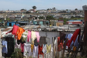 Metal and wooden shacks in a shantytown. Colotful clothing hangs on a washing line in the foreground