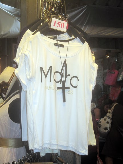 "white t shirt, the word ""Marc"" on the chest, on display on a hangar ..."