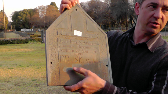 Man holding a slate headstone, about 40 cm by 30 cm, with words carved on it
