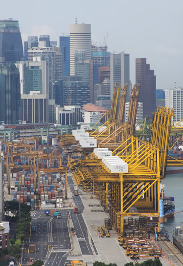 A row of cargo containers on the quayside at Singapore harbor, with the high-rise building of the city center in the background.
