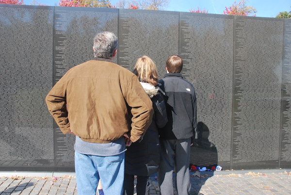 Three people, their backs to the camera, stand in front of the Wall reading the names inscribed on it
